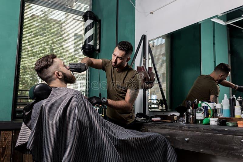Barberaren som klippningar med sax uppsöker av brutal ung man, sitter i stolen framme av spegeln på en frisersalong royaltyfri bild