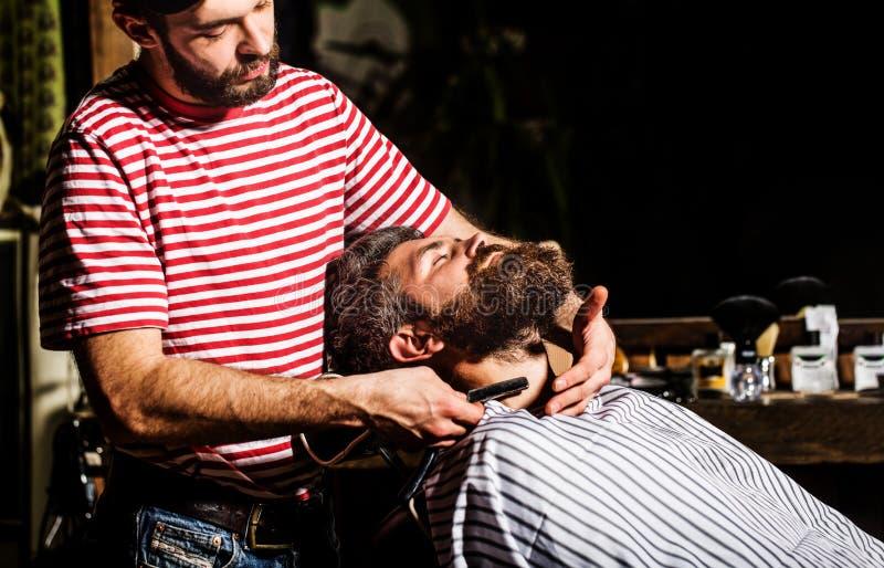 Barberaren som rakar en sk?ggig man i en barberare, shoppar Den uppsökte mannen som sitter i en fåtölj i en barberare, shoppar st royaltyfri foto