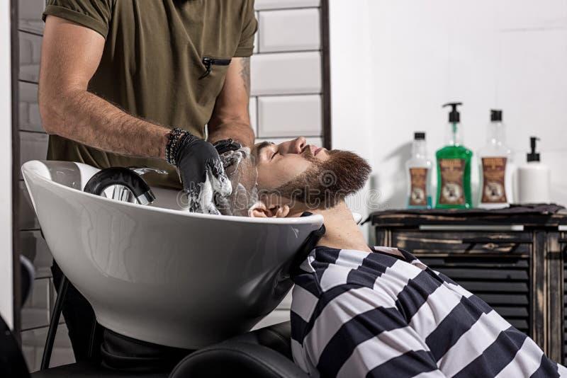 Barberaren tvättar mannens hår i en frisersalong royaltyfri fotografi