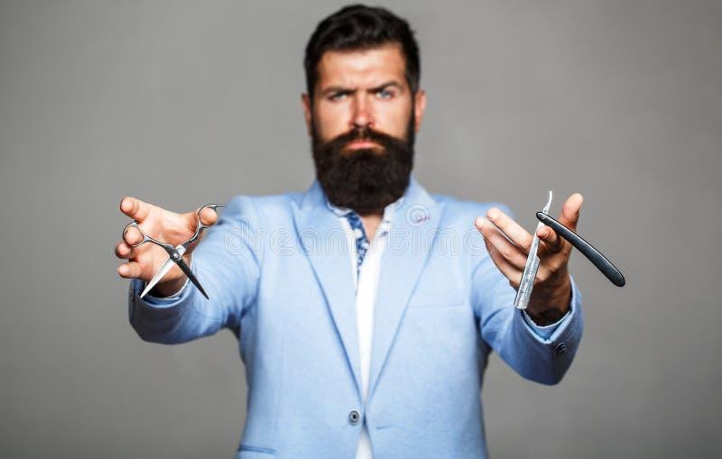 Barberaresaxen och den raka rakkniven, barberare shoppar Man i frisersalong Mäns frisyr i barberare shoppar Mäns frisyr som rakar royaltyfri fotografi