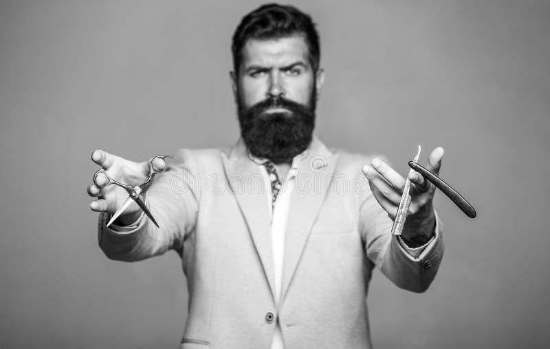 Barberaresaxen och den raka rakkniven, barberare shoppar Man i frisersalong M?ns frisyr i barberare shoppar M?ns frisyr som rakar royaltyfri bild