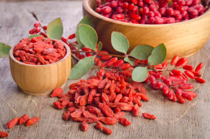 Barberry and dry goji berries in bowls royalty free stock images