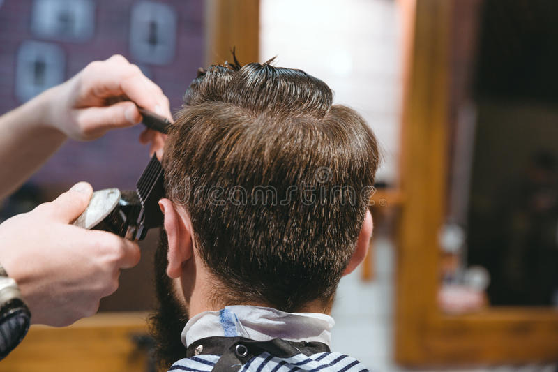 Barbers hands making haircut to man using trimmer. Closeup of barbers hands making short haircut to man using trimmer in barbershop royalty free stock photos