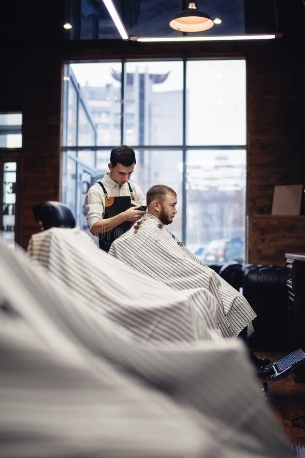 barbershop Barbeiro e cliente na cadeira contra a janela imagens de stock