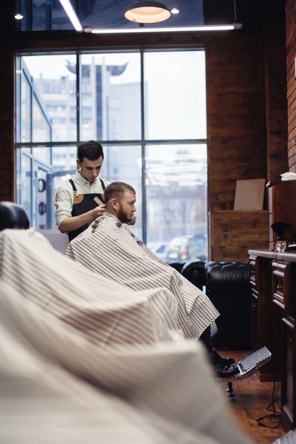 barbershop Barbeiro e cliente na cadeira contra a janela fotografia de stock royalty free