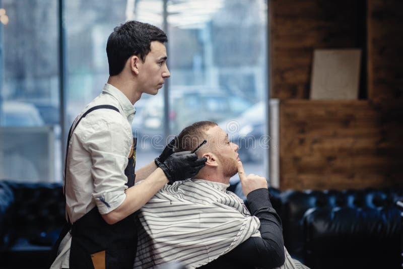 barbershop Barbeiro e cliente na cadeira contra a janela fotos de stock