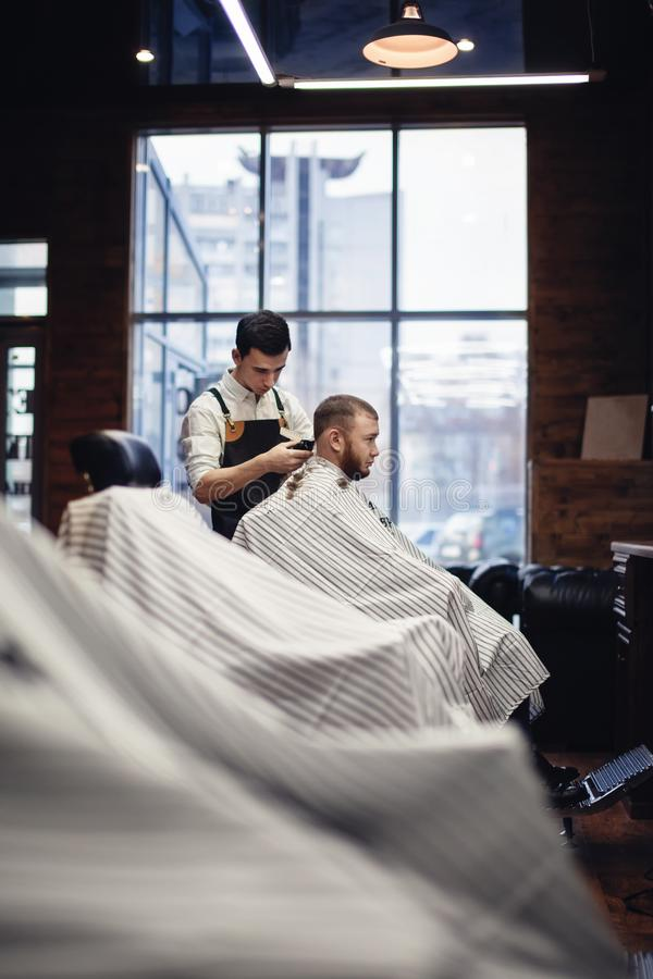 Barbershop. Barber and client in the chair against the window stock images
