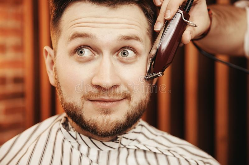 Barbershop Barber shaves his beard to hipster man surprised. Toned photo, vintage style royalty free stock images