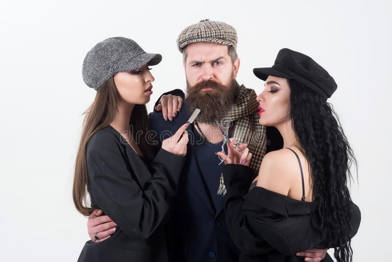 Barbershop. Bearded man with couple of women holding barber tools, barbershop. Barbershop or barber shop. Barbershop for stock images
