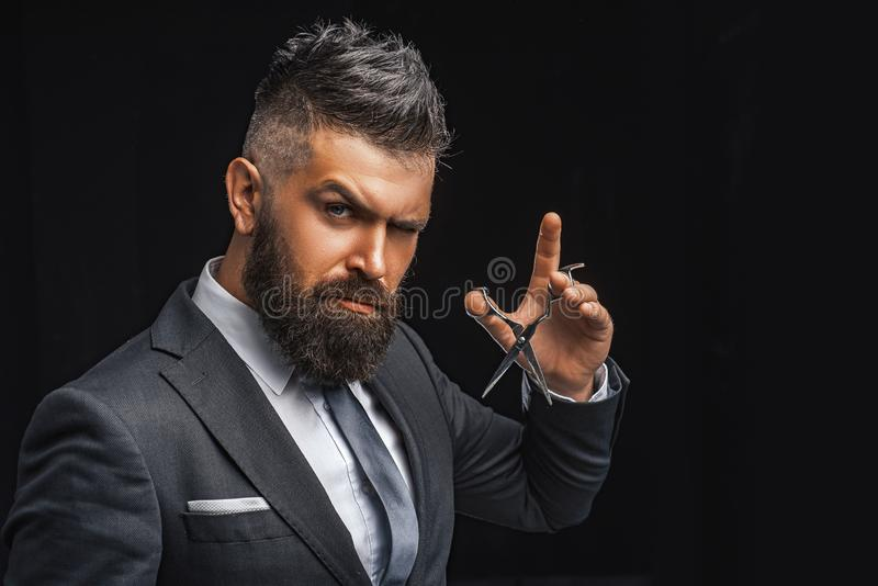 Barbershop concept. Mature hipster with beard. bearded man in formal business suit. brutal male hipster cut hair with. Hairdressing scissors. confident royalty free stock photography