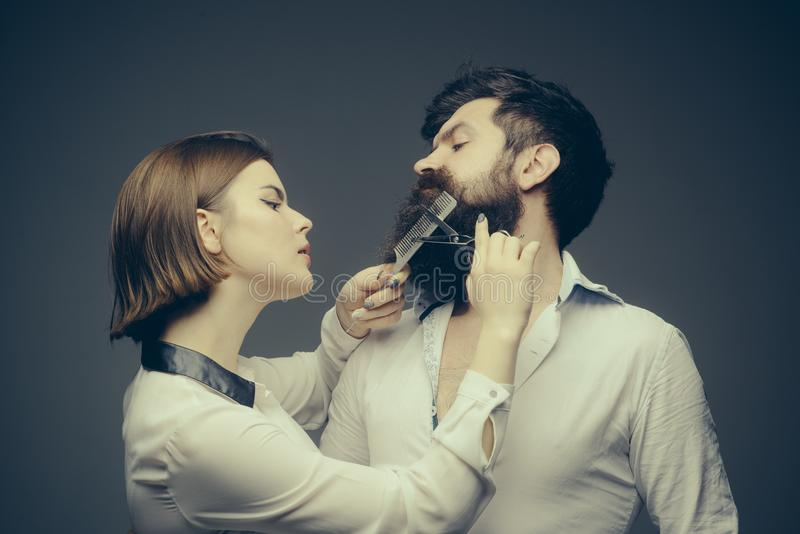 Barbershop or hairdresser concept. Woman hairdresser cuts beard with scissors. Man with long beard, mustache and stylish stock image