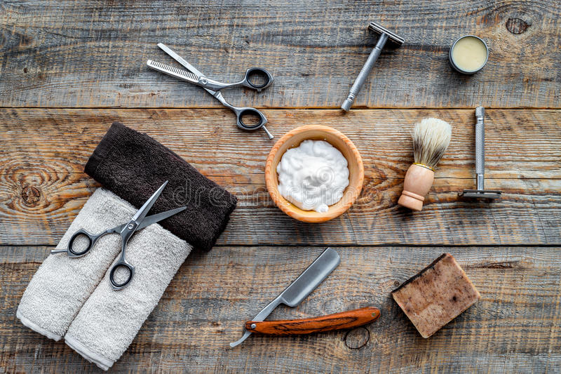 Barbershop. Men`s shaving and haircut. Brush, razor, foam, sciccors on wooden table background top view royalty free stock image