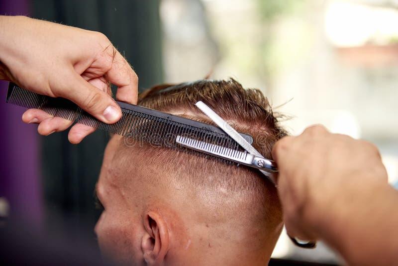 barbershop Mensenkapsel De cliënt krijgt kapsel door zijn kapper stock fotografie