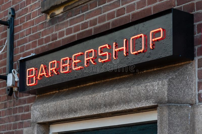 Barbershop neon sign on a brick wall. Red barbershop neon sign on a brick wall in day light royalty free stock images
