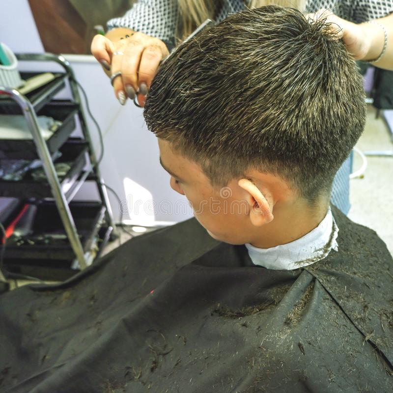 barbershop O close-up dos cortes de cabelo adolescente, mestre faz o corte de cabelo do cabelo na barbearia fotos de stock royalty free