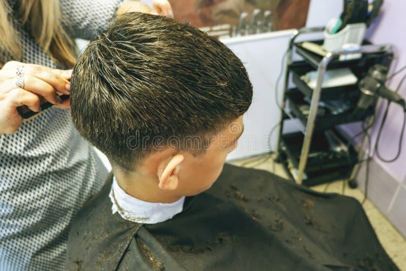 barbershop O close-up dos cortes de cabelo adolescente, mestre faz o corte de cabelo do cabelo na barbearia fotografia de stock