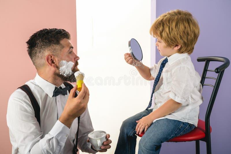barbershop Padre e hijo de moda y elegantes Peluquero que afeita a un hombre barbudo en una peluquer?a de caballeros Barber Shop  fotos de archivo libres de regalías