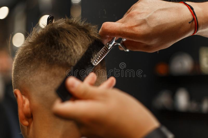 Barbershop. Professional hairdresser makes a man`s hairdo royalty free stock photography
