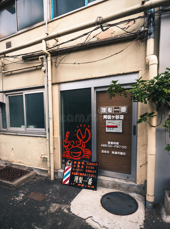 Barbershop sign in Tokyo. Tokyo, Japan - April 18, 2015: Back door of a barbershop with funny cartoon crab character. Writing gives information on opening times royalty free stock images