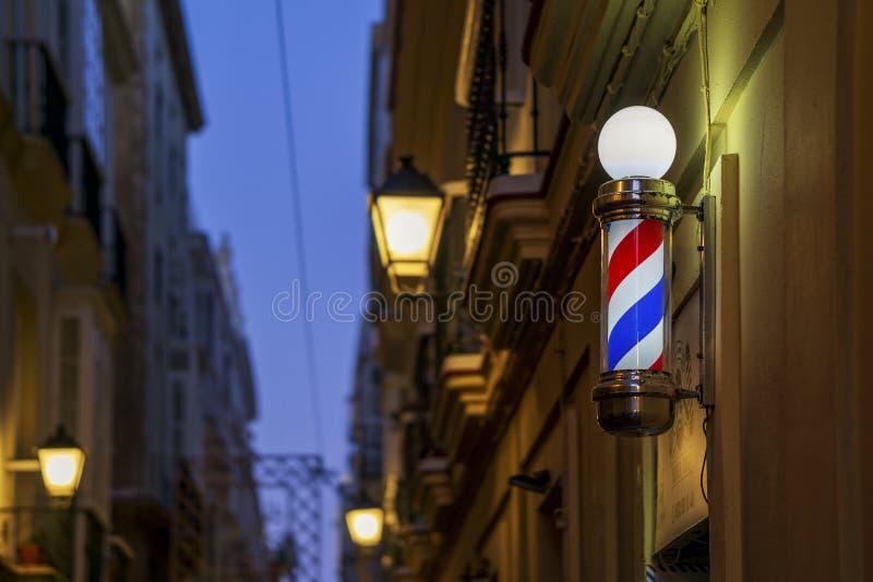 Barbershop - Sinal de luz à noite com luzes de rua desfocadas - Cádiz Andaluzia imagens de stock