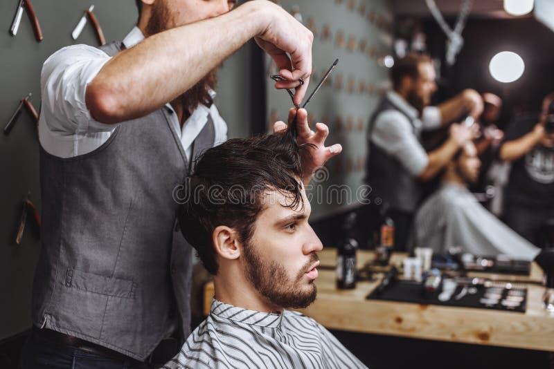 barbershop Uomo con la barba nel negozio di barbiere Salone di capelli moderno immagine stock libera da diritti