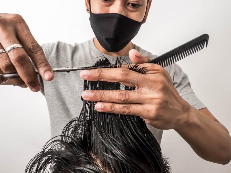 Barbiere attraente con capelli scuri che fanno un taglio di capelli per il cliente con le forbici isolato su fondo bianco immagini stock