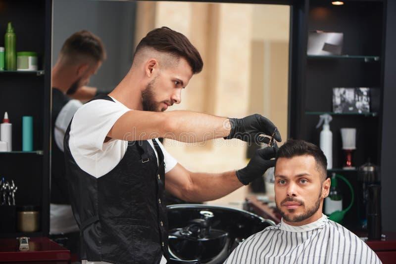 Barbiere che disegna taglio di capelli dell'uomo che usando pettine e le forbici fotografia stock
