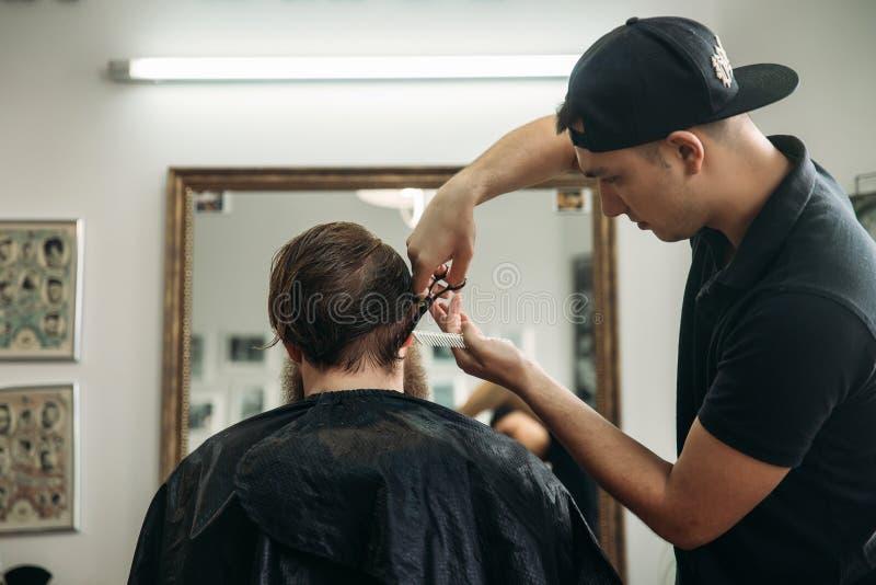 Barbiere che utilizza le forbici e pettine nel parrucchiere fotografie stock libere da diritti