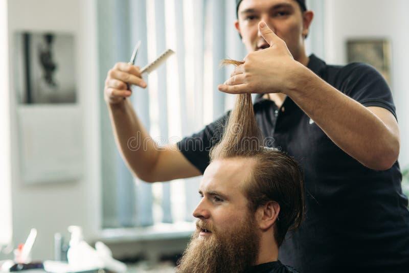 Barbiere che utilizza le forbici e pettine nel parrucchiere immagini stock