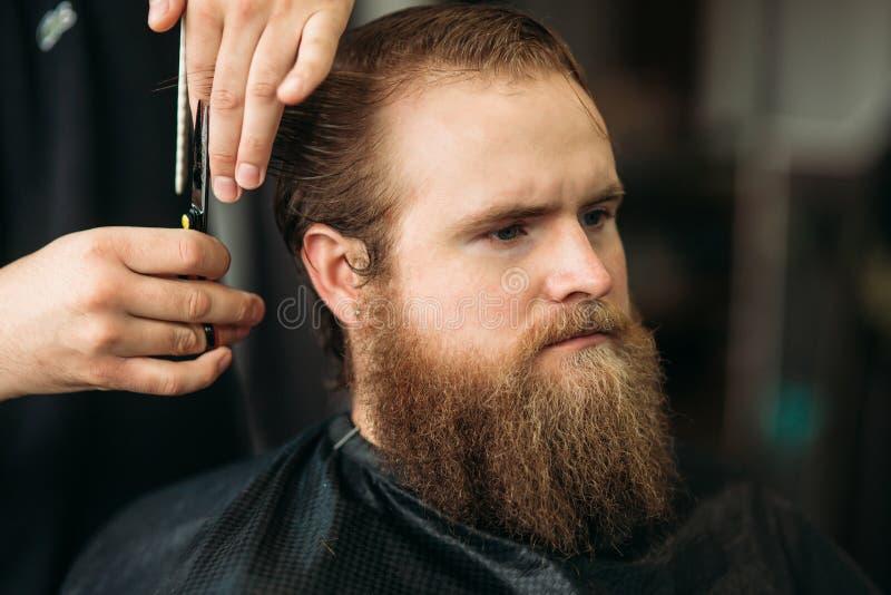 Barbiere che utilizza le forbici e pettine nel parrucchiere immagine stock libera da diritti
