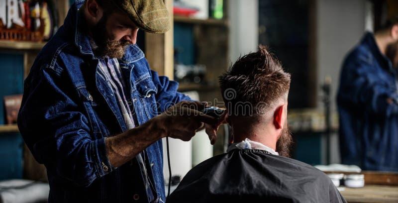 Barbiere con i capelli della guarnizione del tagliatore del cliente, retrovisione Cliente dei pantaloni a vita bassa che ottiene  fotografia stock