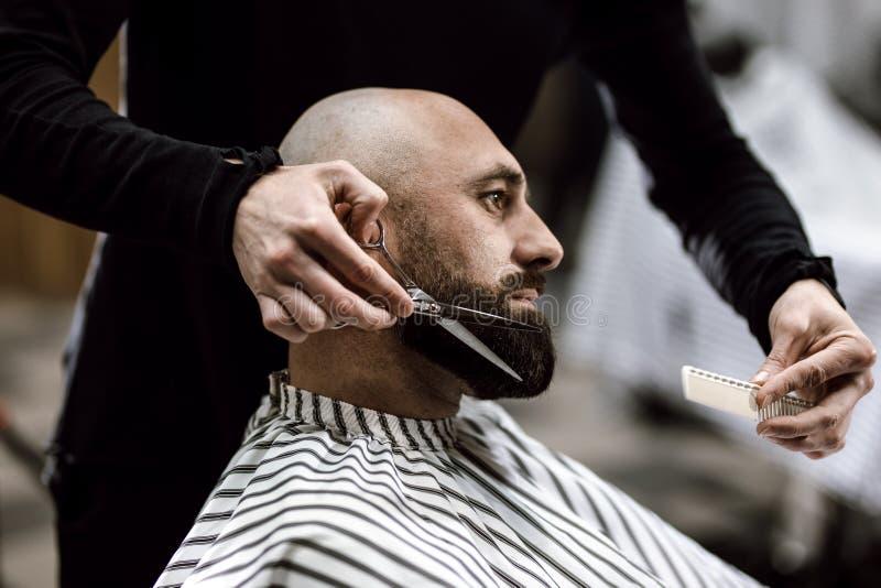 Barbiere di modo vestito in una barba nera di forbici dei vestiti dell'uomo brutale nel parrucchiere alla moda immagini stock