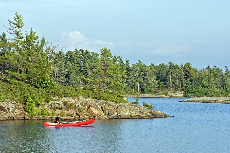 Barbotage d'un canoë sur un lac au Canada photographie stock libre de droits