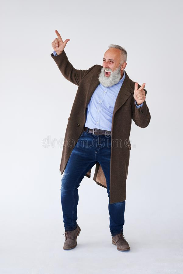 Barbuto maturo bello in cappotto che solleva le mani in studio immagini stock