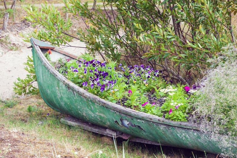 Barca abbandonata decorata con i fiori fotografia stock