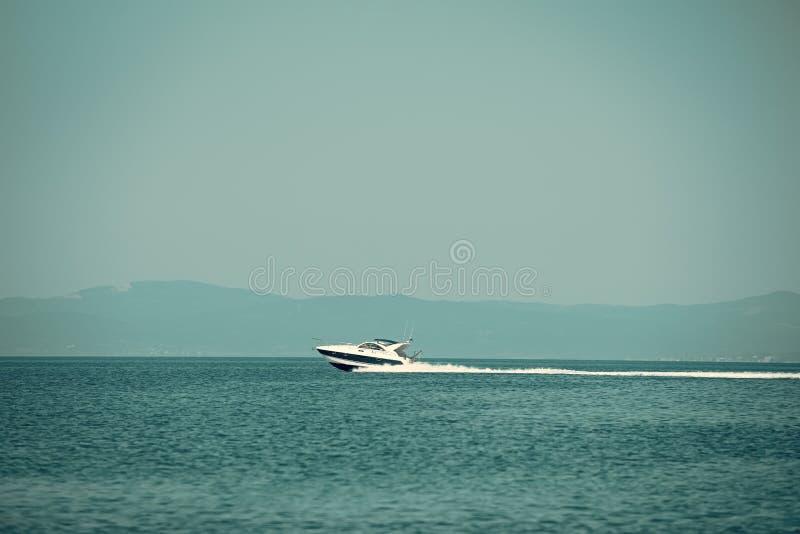 Barca ad alta velocità in mare, cielo blu e montagne su fondo Vista stupefacente sulle scivolate di lusso bianche dell'yacht sull immagine stock libera da diritti