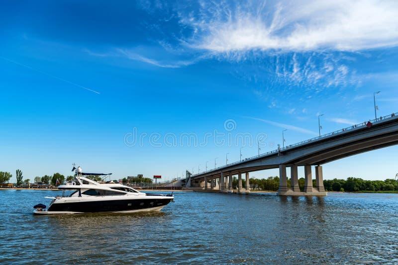 Barca ad alta velocità sul fiume e ponte il giorno soleggiato immagine stock libera da diritti