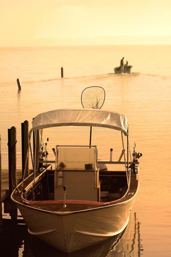 Barca all'indicatore luminoso di Sun di primo mattino fotografia stock