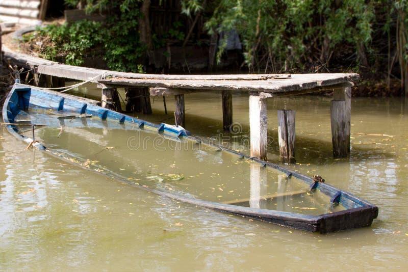 Barca annegata vicino al pilastro del fiume in acqua dolce immagine stock libera da diritti