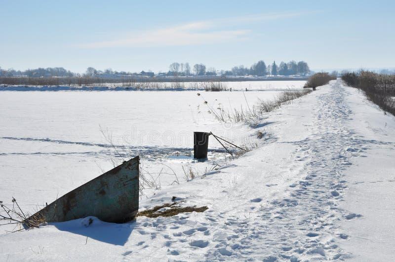 Barca arrugginita ed il lago congelato fotografia stock