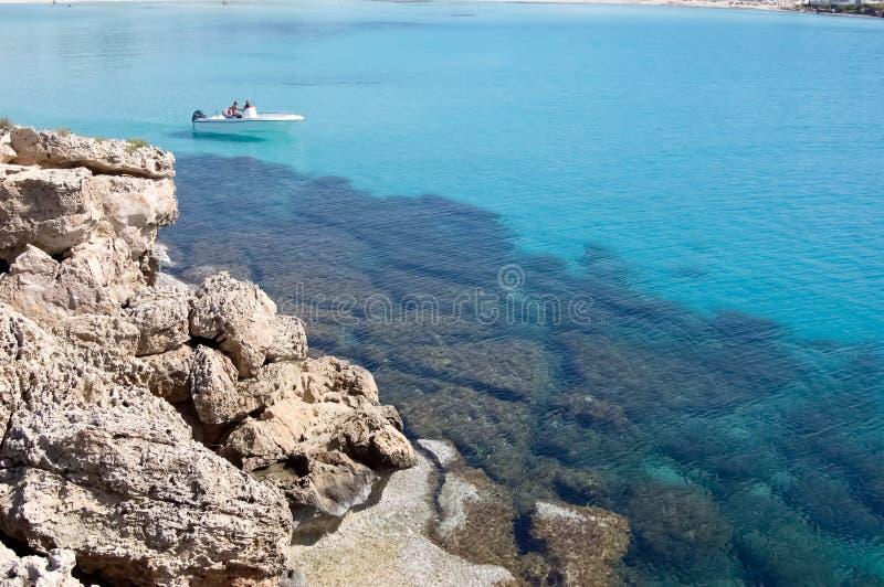 Barca bianca e mare blu trasparente vicino alla riva rocciosa nel Cipro immagini stock libere da diritti