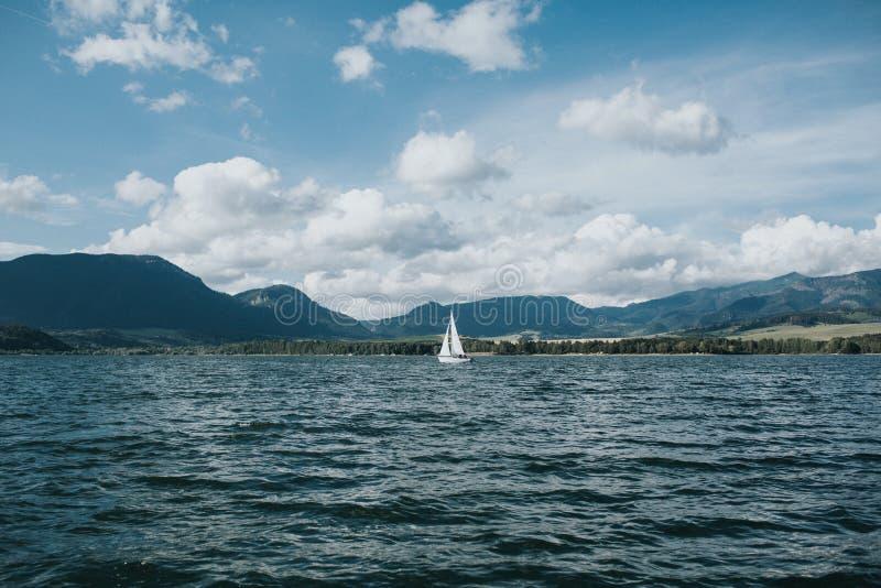Barca bianca sola in lago blu immagini stock libere da diritti