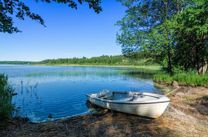 Barca bianca sulla costa norvegese del lago fotografie stock libere da diritti