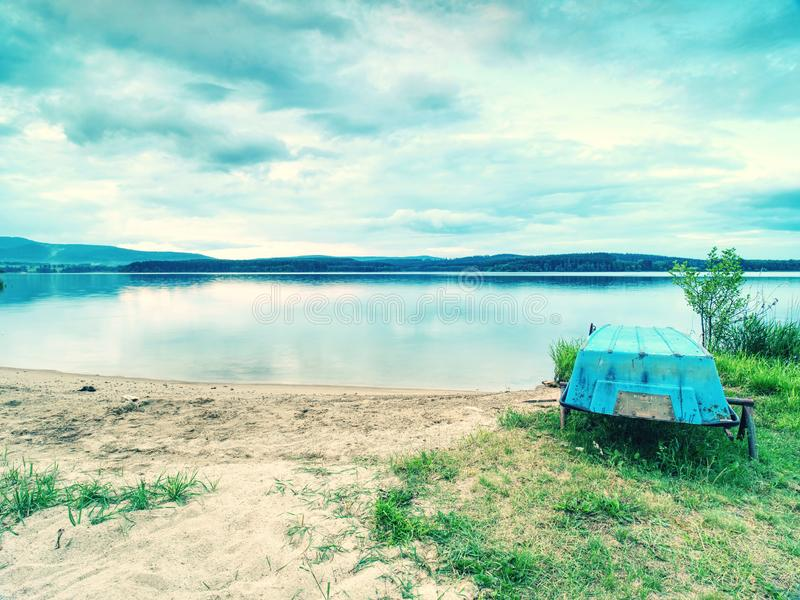 Barca blu ancorata sulla sabbia da spiaggia del lago Livello uniforme immagini stock libere da diritti
