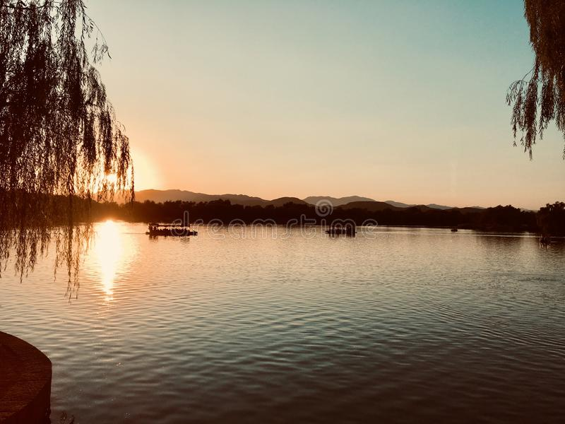 Barca che si dirige sul lago al tramonto fotografia stock libera da diritti
