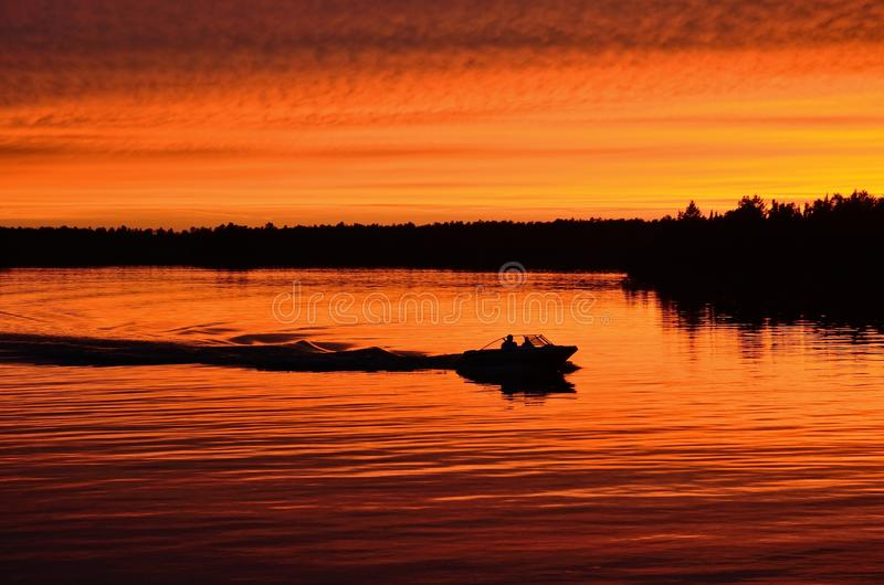 Barca che va in automobile dopo il tramonto fotografia stock