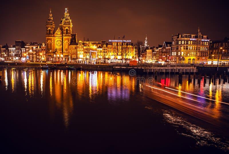 Barca con sfuocatura leggera passando i canali di notte di Amsterdam fotografie stock libere da diritti