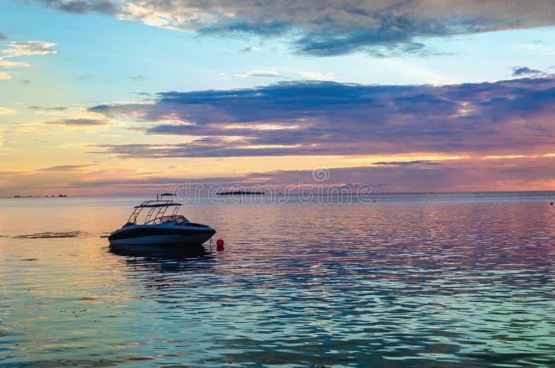 Barca contro un tramonto variopinto sopra l'oceano fotografie stock