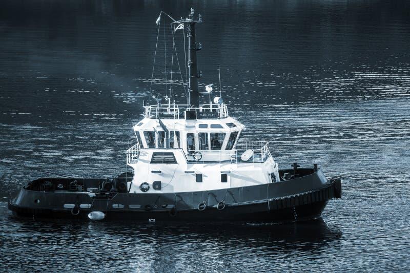 Barca in corso, blu del rimorchiatore di Persevero tonificato fotografia stock libera da diritti