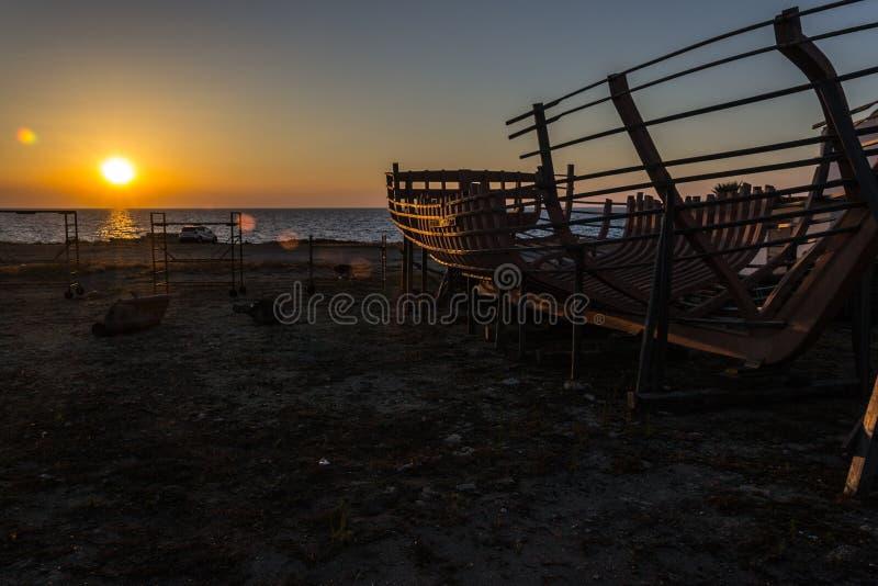 Barca dalla spiaggia al tramonto fotografie stock libere da diritti